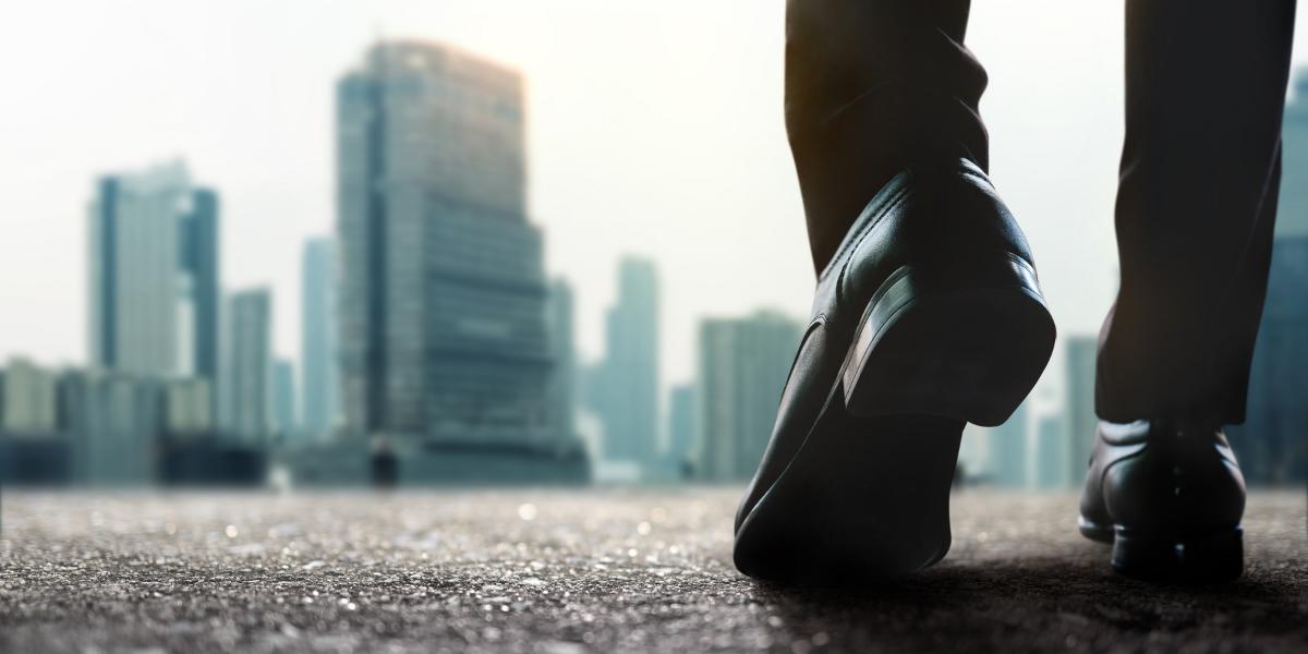 close up of man's shoes, slowly walking toward city