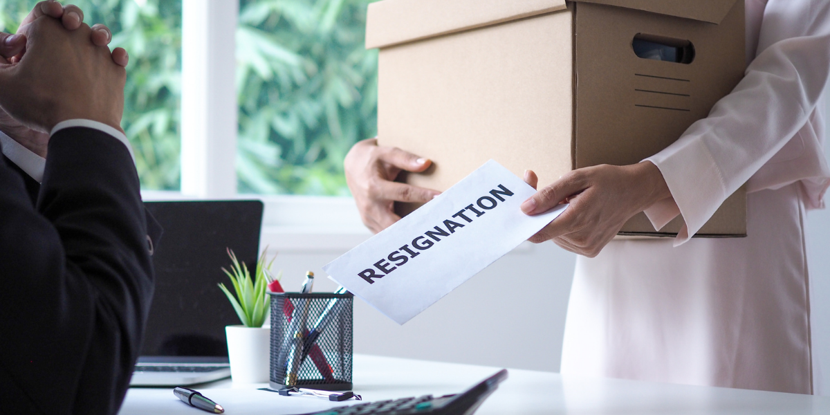 Woman holding a box while handing a resignation letter to her employer