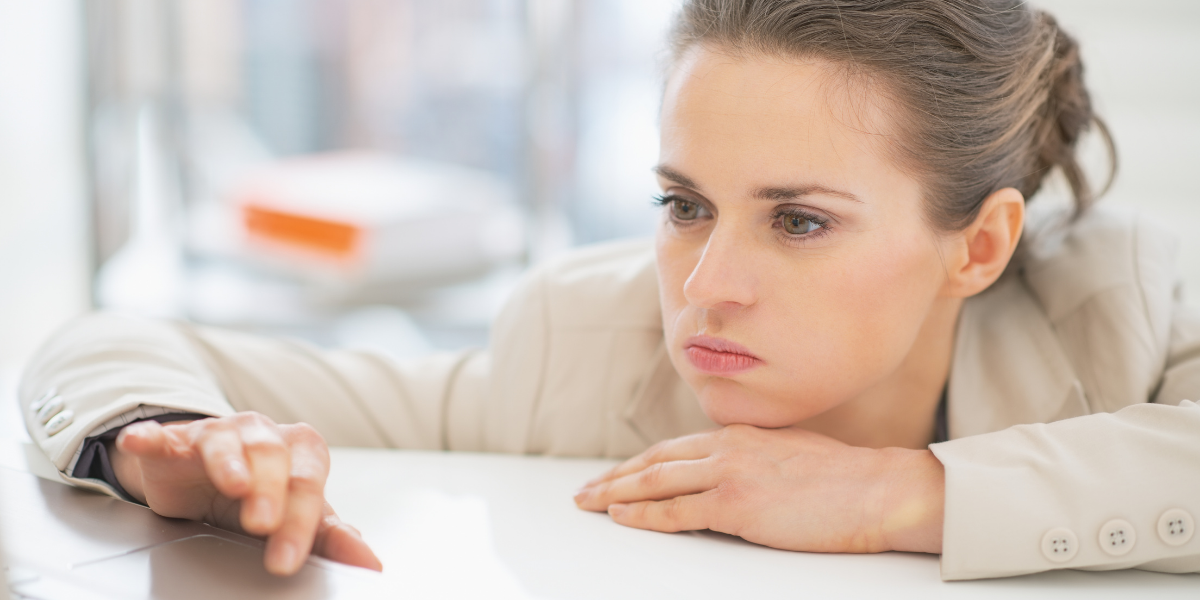 Woman staring blankly at computer, resting chin on hand, needing a boost in morale.